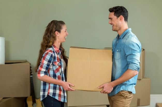 新しい家でカートンボックスを開梱しながら直面している若いカップル