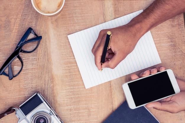カメラと眼鏡のテーブルの上にスマートフォンを押しながらメモ帳に書いて実業家の画像をトリミング