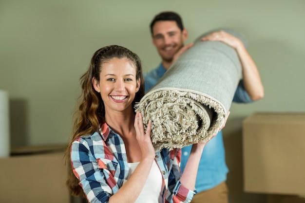 幸せなカップルを運ぶ彼らの新しい家で敷物を重ね