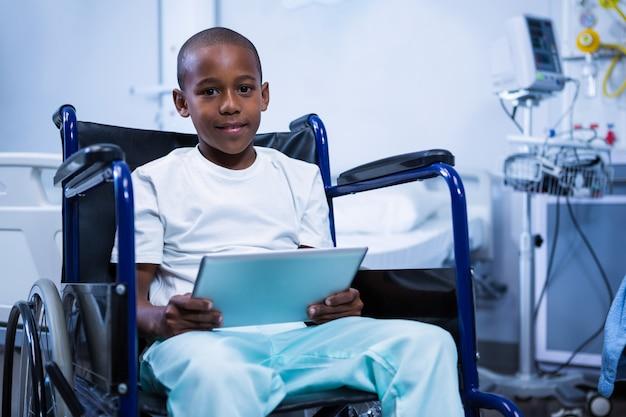 Портрет мальчика, сидящего на инвалидной коляске с цифровым планшетом в палате