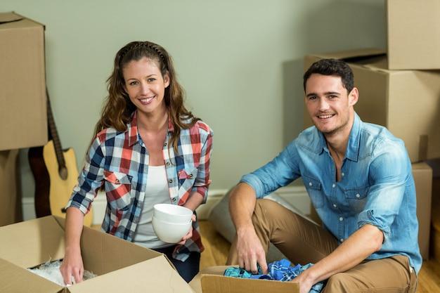 若いカップルが彼らの新しい家で箱を開梱