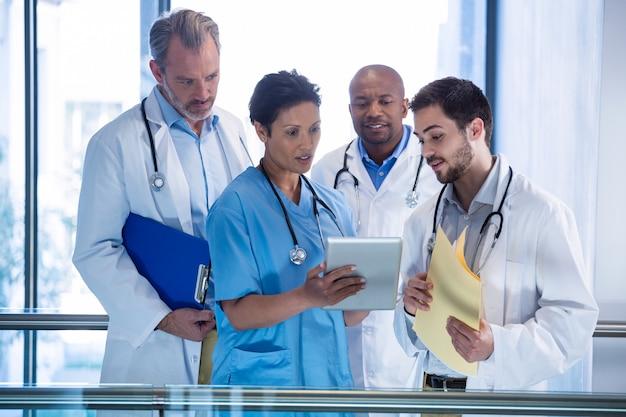 男性医師と看護師が廊下でデジタルタブレットを使用して