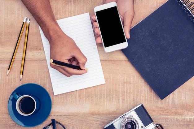 カメラとテーブルの上の眼鏡でスマートフォンを押しながらメモ帳に書いて実業家の高角度のビュー