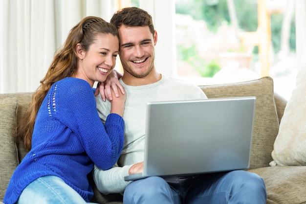 若いカップルがソファーに座っていたとリビングルームでラップトップを使用して