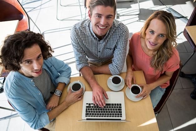 Трое друзей с чашками кофе, используя ноутбук в кафе