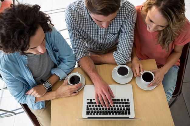 Трое друзей с чашками кофе, используя ноутбук