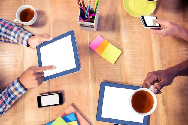 Обрезанное изображение деловых людей, использующих технологии во время кофе в офисе