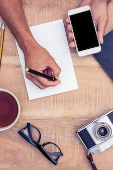カメラとコーヒーテーブルの上にメモ帳に書いている間スマートフォンを保持している実業家の高角度のビュー