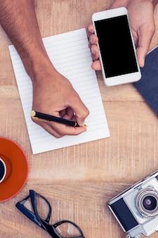 カメラとテーブルの上のコーヒーでメモ帳に書いている間スマートフォンを持っているビジネスマン手のハイアングル