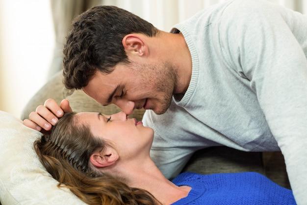 リビングルームのソファーにキスをする若いカップル