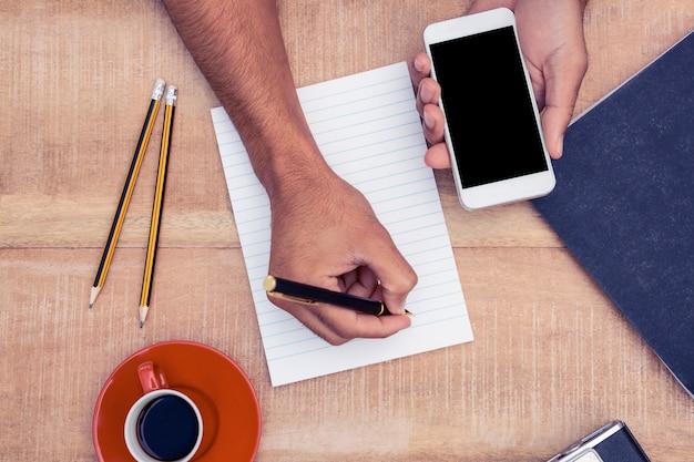 カメラとテーブルの上のコーヒーでメモ帳に書いている間スマートフォンを持っているビジネスマン手のオーバーヘッドビュー