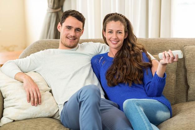 リビングルームのソファーで一緒にテレビを見ている若いカップルの肖像画