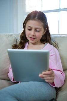Девушка с помощью цифрового планшета во время отдыха на диване