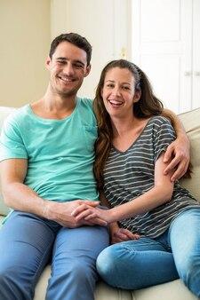 リビングルームのソファーに座っていた若いカップルの肖像画