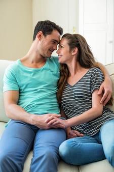 リビングルームのソファーに寄り添う若いカップル