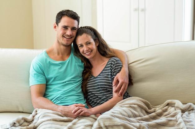 リビングルームのソファーで抱きしめる若いカップルの肖像画