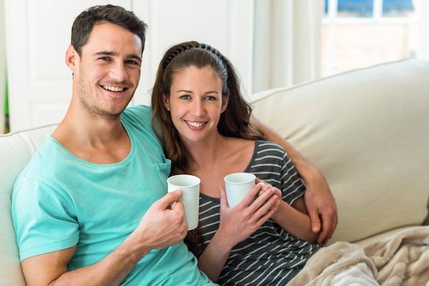 リビングルームのソファーでコーヒーを飲んでいる若いカップルの肖像画