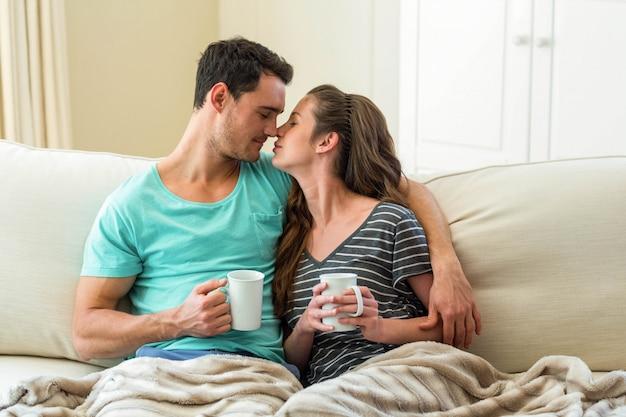リビングルームでコーヒーを飲みながらソファに寄り添う若いカップル