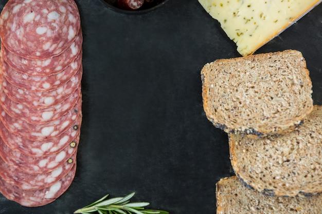 サラミ、チーズ、スレートプレート上の茶色のパンのスライス