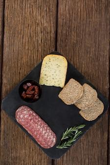 サラミ、チーズ、ローズマリーハーブ、スレートプレートに茶色のパンのスライス