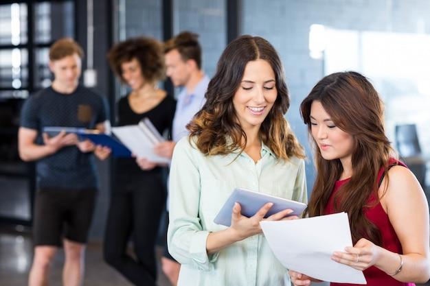 デジタルタブレットを見て、同僚がオフィスで後ろに立っている間議論をしている女性