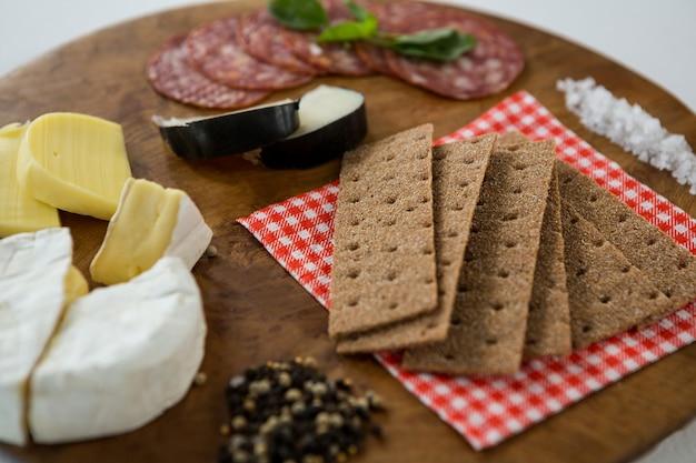 さまざまなチーズ、木の板にサラミ、クラッカー、スパイス、海の塩