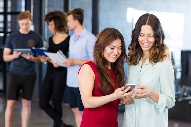 女性がスマートフォンを見ていると、同僚がオフィスで後ろに立っている間議論をしています