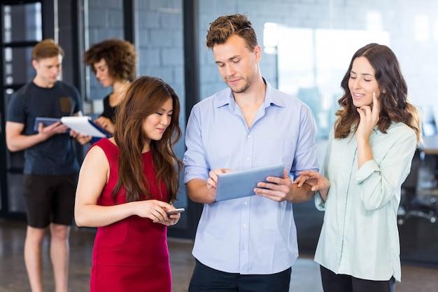 Коллеги смотрят на цифровой планшет и обсуждают в офисе