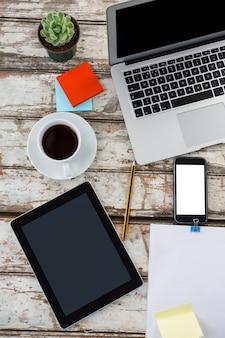コーヒー、ラップトップ、鉢植え、付箋、木製のテーブルの上の携帯電話