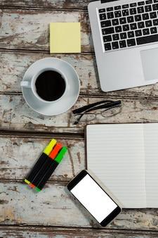 ノートパソコン、スマートフォン、オフィスアクセサリー付きのコーヒーカップ
