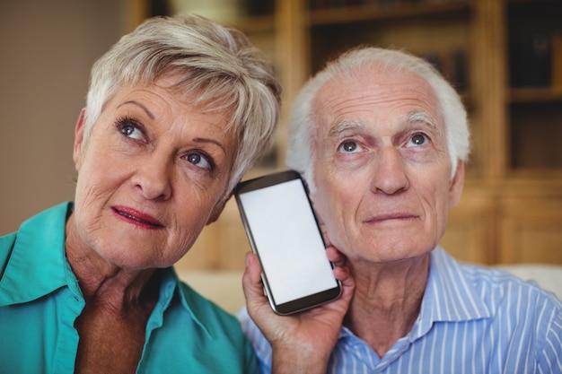 リビングルームで携帯電話を使用して年配のカップル
