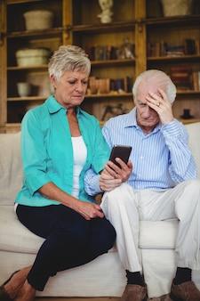 携帯電話を見て緊張した年配のカップル