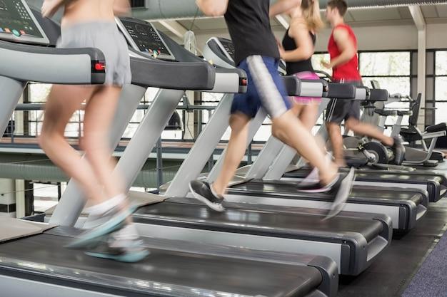 Женщины и мужчины бегают по беговой дорожке в спортзале