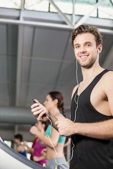 Улыбается мускулистый мужчина на беговой дорожке, слушать музыку в тренажерном зале