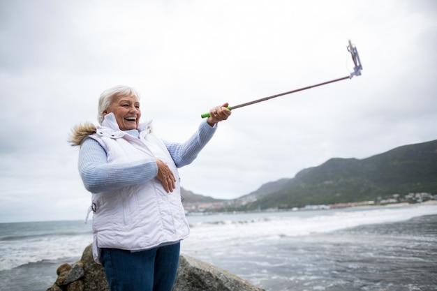 年配の女性が自分撮り棒から自分撮りを取る