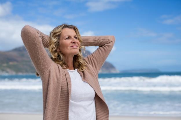 ビーチに立っている頭の後ろに手を持つ成熟した女性