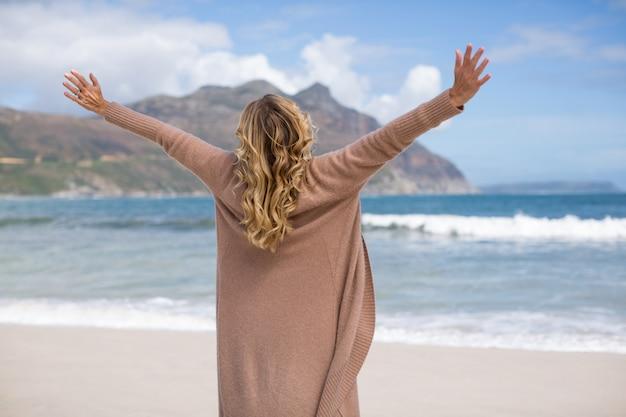 腕を伸ばしてビーチに立っている熟女