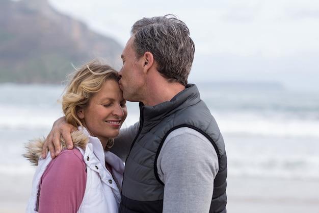 Зрелый мужчина целует женщину в лоб
