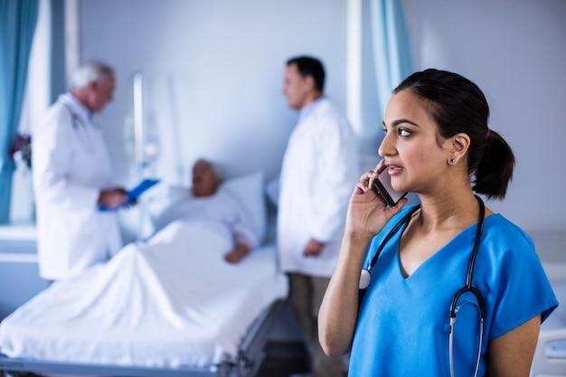 Женщина-врач разговаривает по мобильному телефону в палате