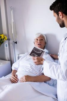 病棟の女性上級患者とデジタルタブレットを介して医療報告書を議論する男性医師