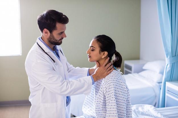 病院で患者の首を調べる医師