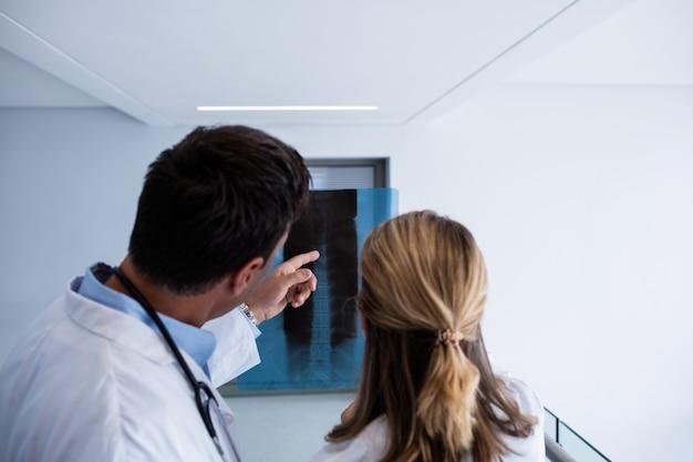 Мужской и женский доктор обсуждая над отчетом рентгеновского снимка