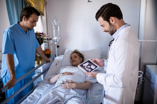 Мужской доктор смотря отчет о сонографии на цифровой таблетке