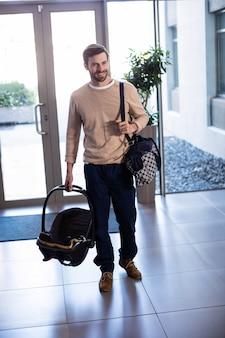病院でベビーキャリアとバッグを持って男