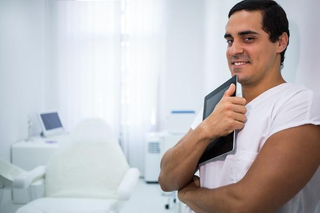 Усмехаясь доктор держа цифровую таблетку на клинике
