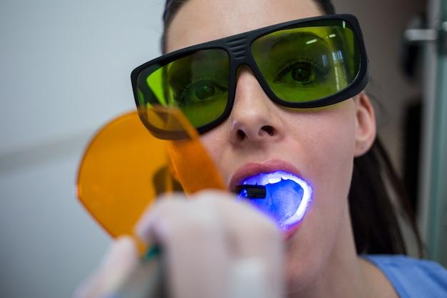 歯科医が患者の歯を歯科用硬化ライトで調べる