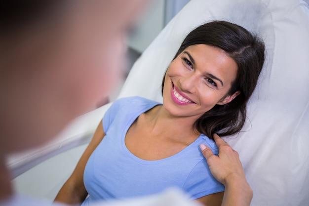 Женский пациент улыбается во время разговора с врачом