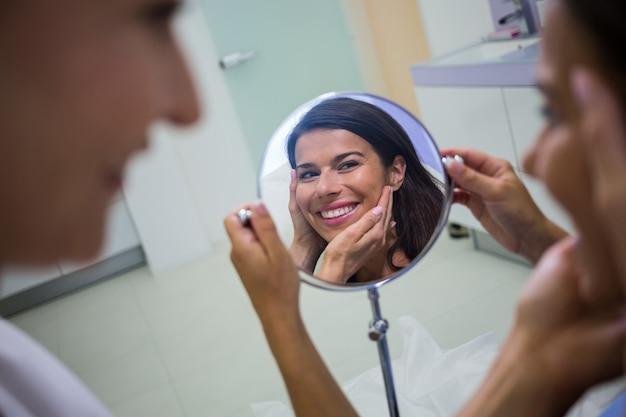 美容治療を受けた後、鏡で肌をチェックする女性