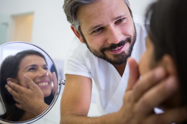 医師は美容治療後に患者の皮膚をチェック