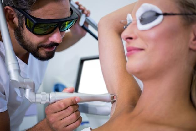 皮膚科医が患者の脇の下の毛を取り除く